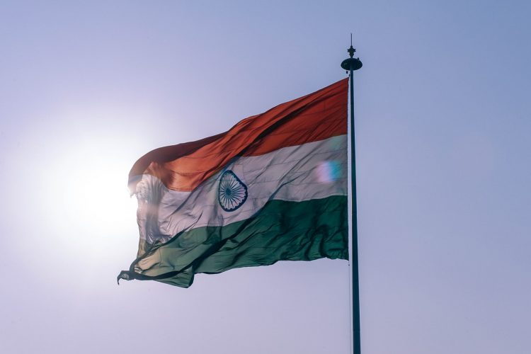 The India flag waving in the breeze over a sunlit sky