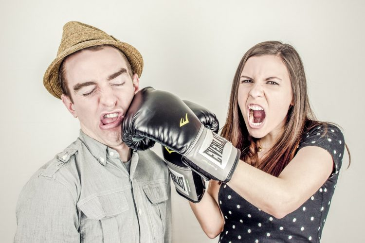 Woman wearing boxing gloves and punch a man in the face